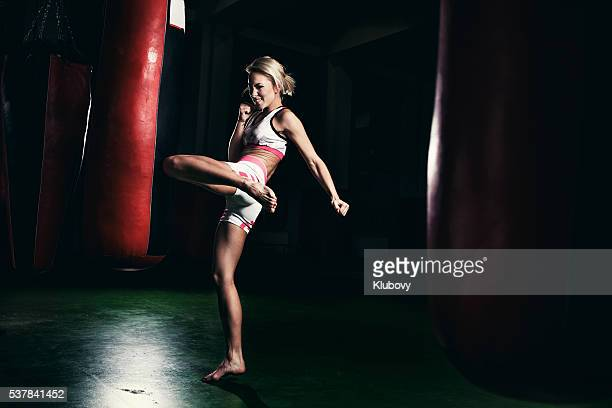 female kickboxer fighter training with a punching bag - muay thai stock pictures, royalty-free photos & images