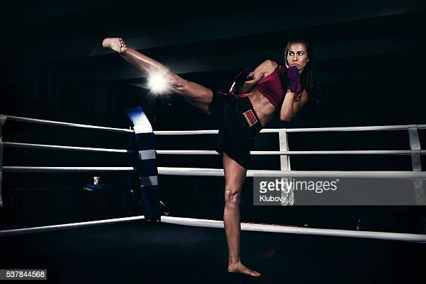 Female kickboxer training in a boxing ring