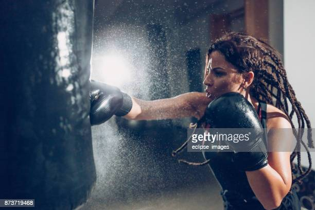 Female kickboxer training with a punching bag