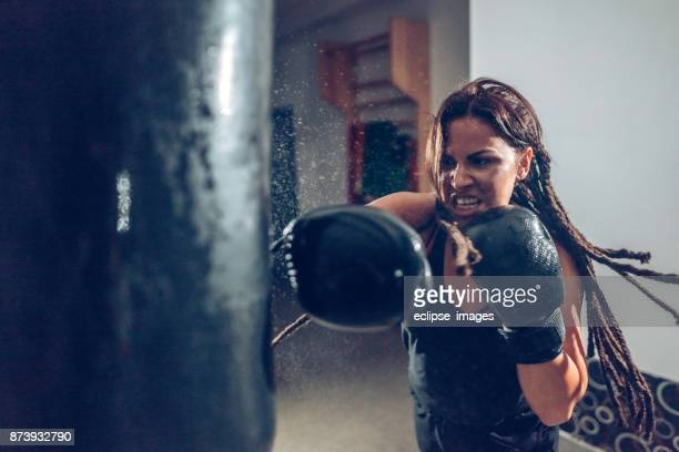female kickboxer training with a punching bag - furioso foto e immagini stock