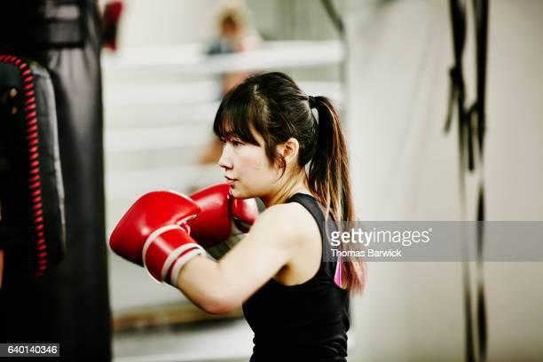 female kickboxer working out in fighting gym - artes marciales fotografías e imágenes de stock