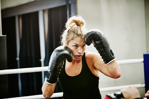 Female kickboxer working out in ring in gym - gettyimageskorea