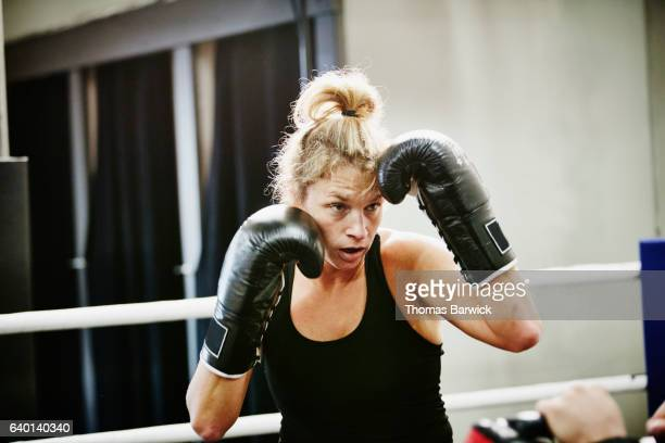 Female kickboxer working out in ring in gym