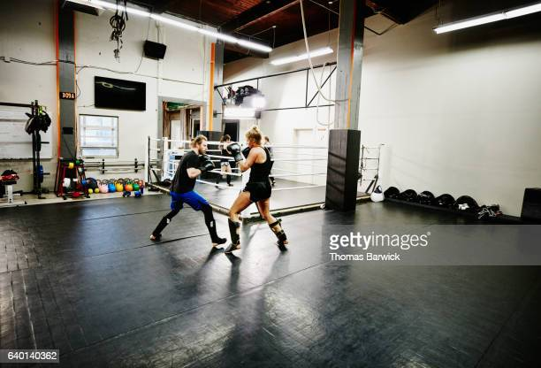 Female kickboxer working out with trainer in gym