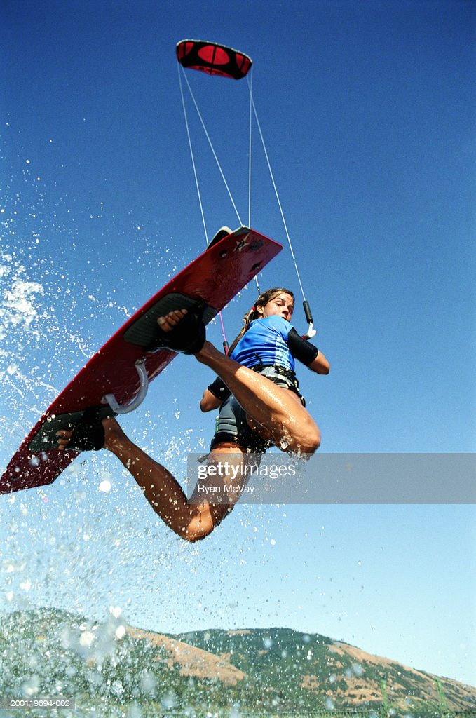 Female kiteboarder in mid-air, looking over shoulder, low angle view : Stock Photo
