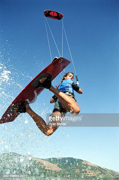 Female kiteboarder in mid-air, looking over shoulder, low angle view
