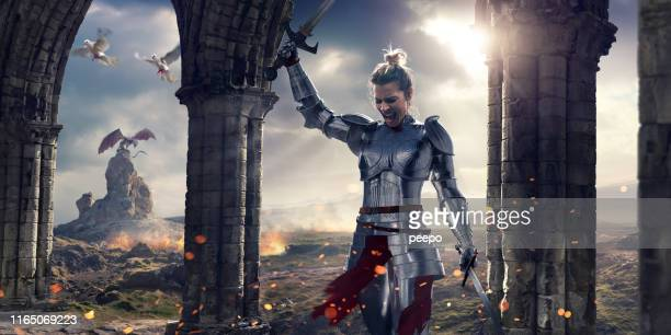 female knight screaming after battle holding swords near stone pillars - medieval stock pictures, royalty-free photos & images