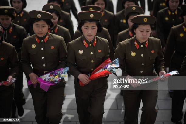 TOPSHOT Female Korean People's Army soldiers arrive to pay their respects before the statues of late North Korean leaders Kim Il Sung and Kim Jong Il...
