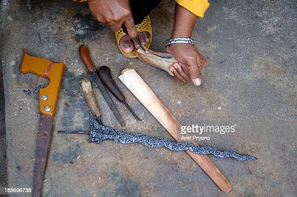 Female kris maker Hj Mariana making kris sheaths in a section of the traditional market in Setono Betek in Kediri East Java Working from the market...