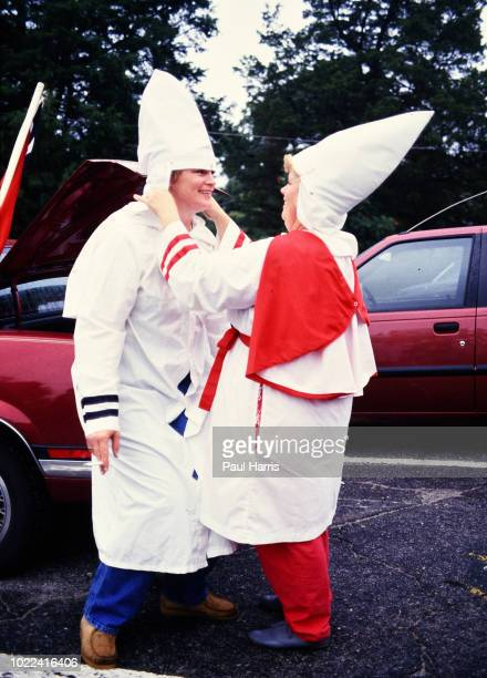 Female Ku Klux Klan members adjust their hoods before a march May 4, 1989 in Stone Mountain , Georgia