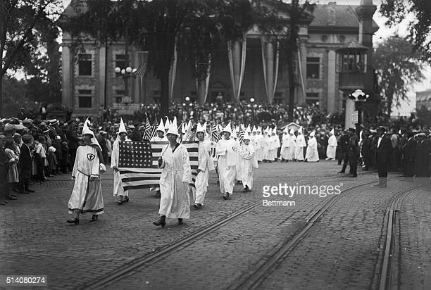 Female Ku Klux Klan members march through Binghamton NY holding an American flag in the 1920s
