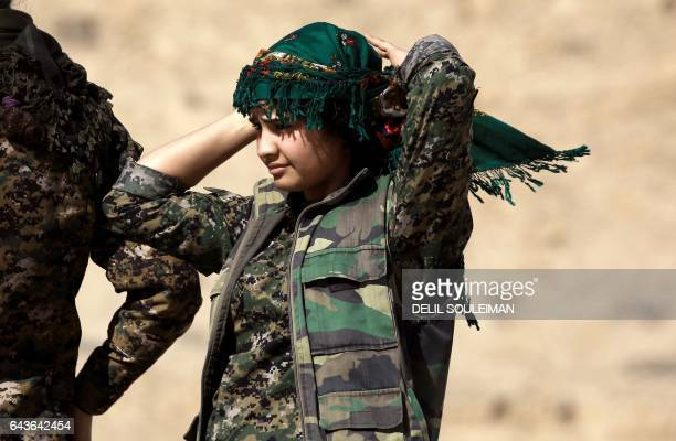 TOPSHOT A female Kurdish fighter and member of the USbacked Syrian Democratic Forces made up of an alliance of Arab and Kurdish fighters adjusts her...
