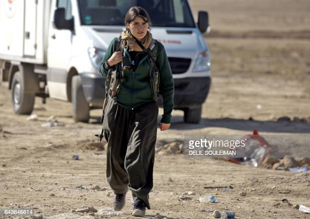 A female Kurdish fighter of the USbacked Syrian Democratic Forces made up of an alliance of Arab and Kurdish fighters walks in the village of Sabah...