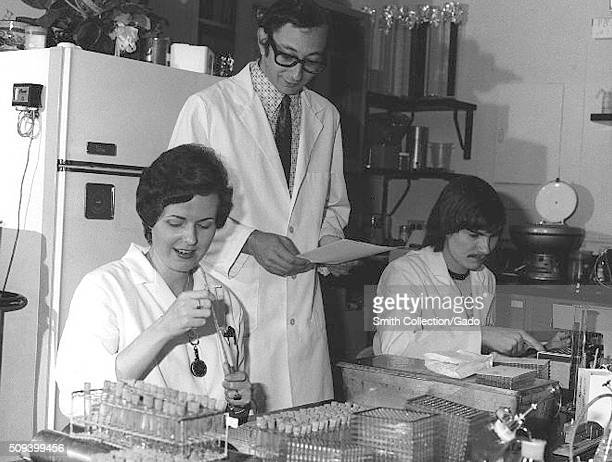 Female lab technicians reading and checking serologies to determine presence of influenza A/NJ/8/76 and registering antibody rise to the swine...
