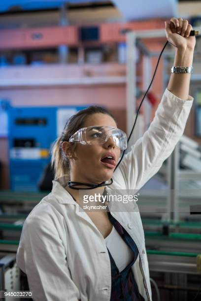 female lab worker trying to strange herself of boredom in laboratory. - one young woman only stock pictures, royalty-free photos & images