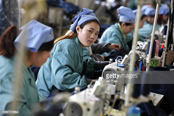 Female labours works at a cloth factory in Huaibei city Anhui province east China on 19th Jan 2016 China's economy grew at its slowest rate in a...