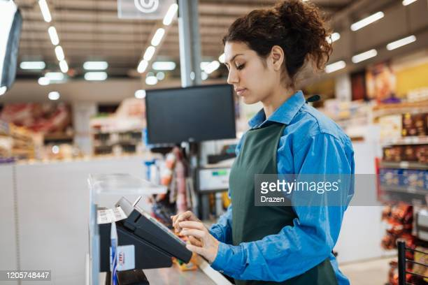 female latina employee in supermarket - cashier stock pictures, royalty-free photos & images