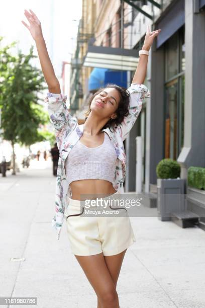a female latinx millennial stretches her arms over her head showing a sense of freedom. - crop top stock pictures, royalty-free photos & images