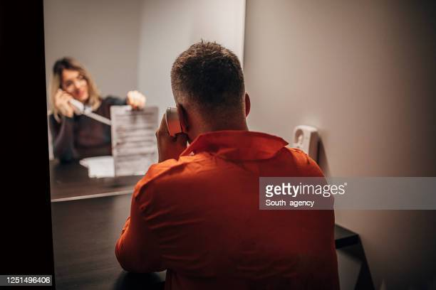 female lawyer and prisoner sitting in visiting room - confession law stock pictures, royalty-free photos & images