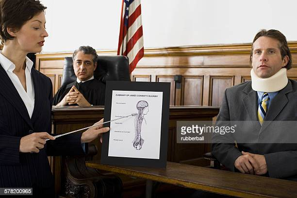female lawyer pointing at an exhibit in front of a judge and a victim - evidence stock pictures, royalty-free photos & images