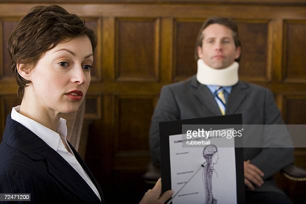 A female lawyer pointing at evidence in front of a victim in a courtroom