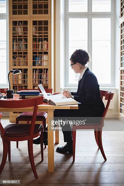 Female lawyer using laptop while sitting at table in library