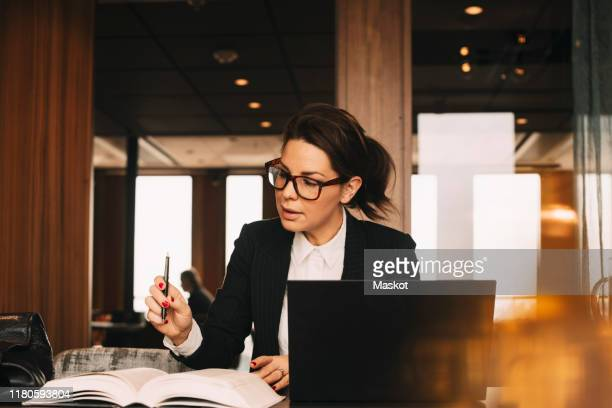 female lawyer with laptop concentrating while reading book at office - bedrijven financiën en industrie stockfoto's en -beelden