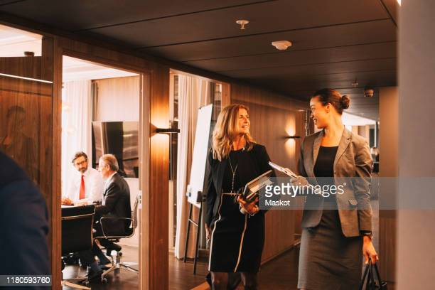 female lawyers discussing while colleagues planning in background at law office - advocaat juridisch beroep stockfoto's en -beelden