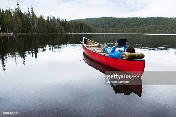 A female laying in a canoe.