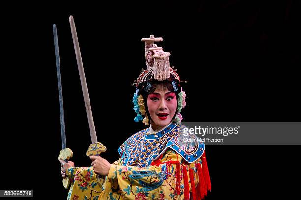 A female lead actor in traditional costume and swords pictured during a performance of Peking Opera for tourists at a theatre in Beijing China Peking...