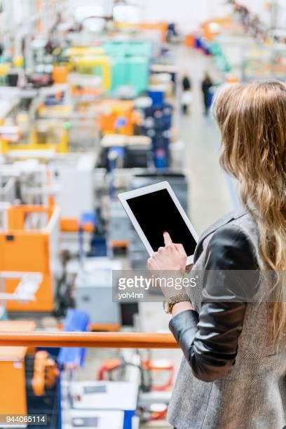 Femme comme chef de l'usine à l'aide de tablette numérique