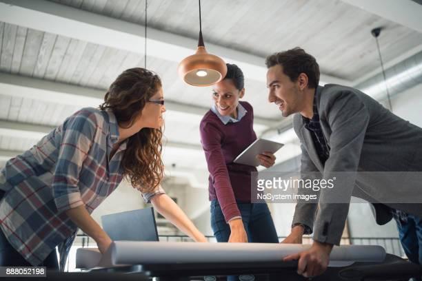 Mujeres líderes. Tres arquitectos jóvenes y creativas, trabajando juntos, examinar el plan de acción