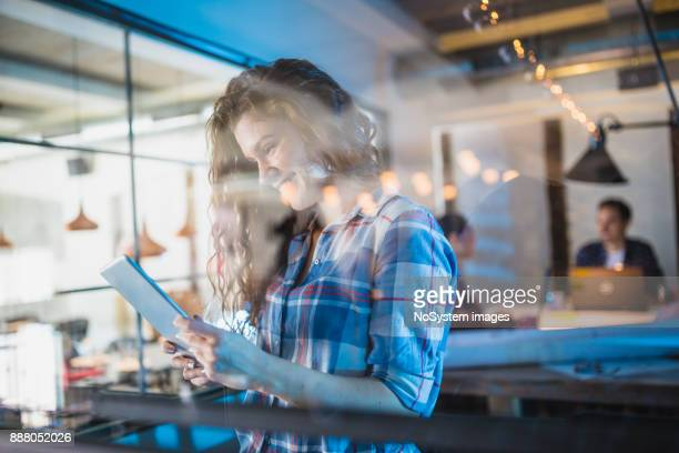 Female Leaders. Young redhead, woman architect using digital tablet in front of architecture studio.