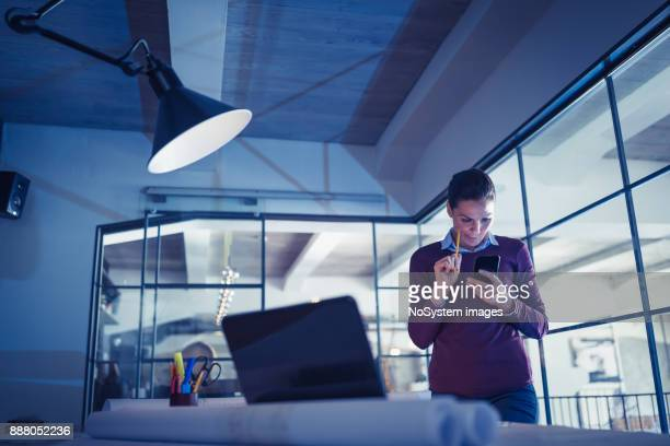 Female Leaders. Young woman architect (designer), working on a project late at night in architecture studio