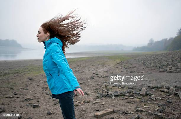 female leaning into wind with hair flying