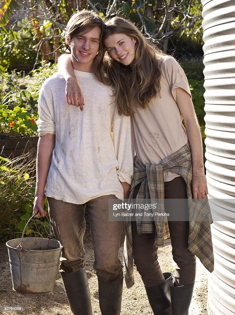 Female leaning on male next to water tank : Stock Photo
