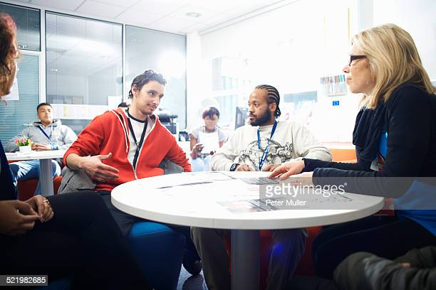 Female lecturer and a group of college students having informal discussion in classroom