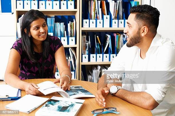 Female lecturer having tutorial with male student in college classroom