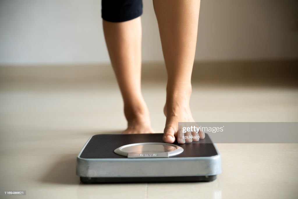 Female leg stepping on weigh scales. Healthy lifestyle, food and sport concept. : Stock Photo