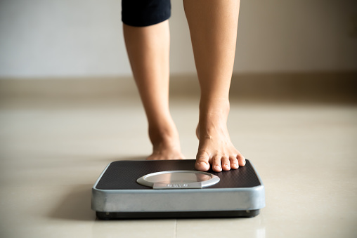 Female leg stepping on weigh scales. Healthy lifestyle, food and sport concept. 1169486621