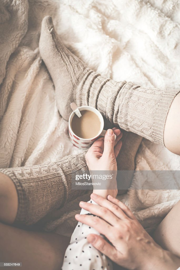 Female legs in knitted socks with cup of  coffee : Stock Photo