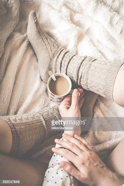 female legs in knitted socks with cup of  coffee - white women feet stock pictures, royalty-free photos & images