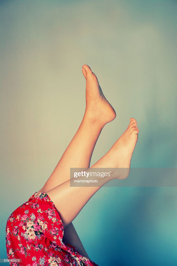 Female legs raised with red floral skirt : Foto de stock