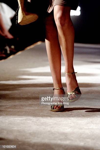 Female Legs Walking on Runway in Gold Heels