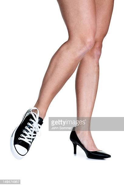 female legs wearing a sneaker and high heel shoe - pump dress shoe stock photos and pictures