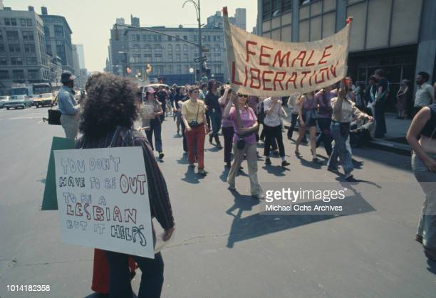 A 'Female Liberation' banner at an LGBT parade through New York City on Christopher Street Gay Liberation Day 1971 One person carries a placard...