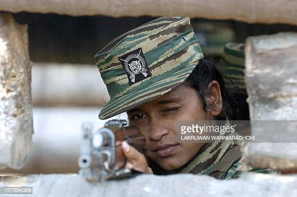 Female Liberation Tigers of Tamil Eelam guerrillas aim their weapons as they stand in a bunker located near the rebel front 03 July 2006 north of the...