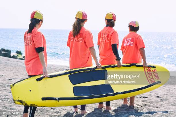 female life savers of various ages have a rescue board - generic location stock pictures, royalty-free photos & images