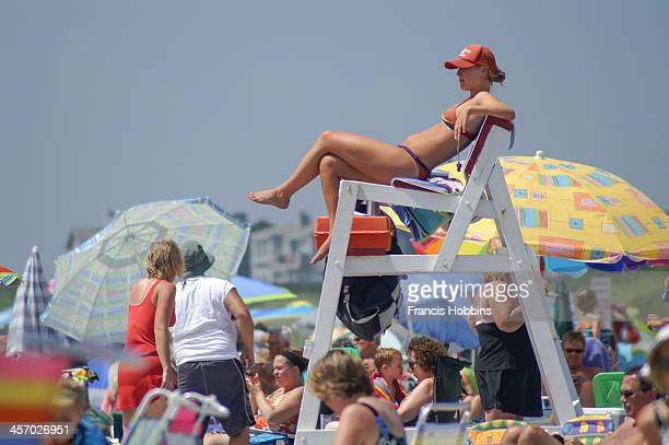 CONTENT] Female lifeguard in a two piece bathing suit on duty at Roger Williams State beach also known as Sand Hill Cove on a sunny summer day