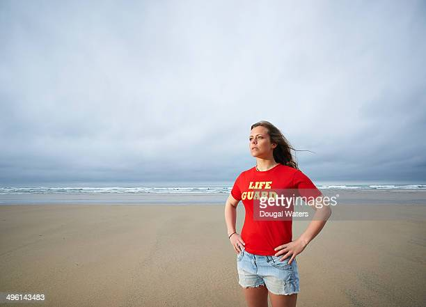 Female lifeguard standing on Atlantic beach.